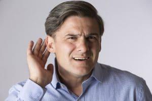 Studio Shot Of Man Suffering From Hearing Loss