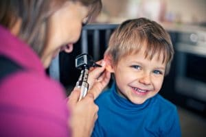 Young boy getting his ears examined by a female doctor