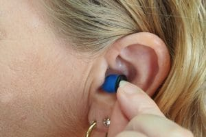 Woman places ear plug in her ear.