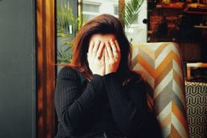 Woman covers her face.