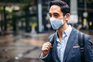 Man with hearing aid wears a mask outside.