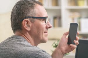 A man with a hearing aid looks at his phone.