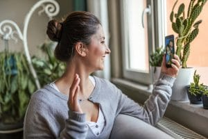 Woman with a hearing aid uses a phone.